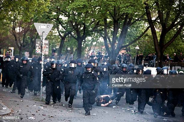 German riot policemen overrun a protester after a march on May Day on May 2016 in Berlin Germany Tens of thousands of people across Germany...