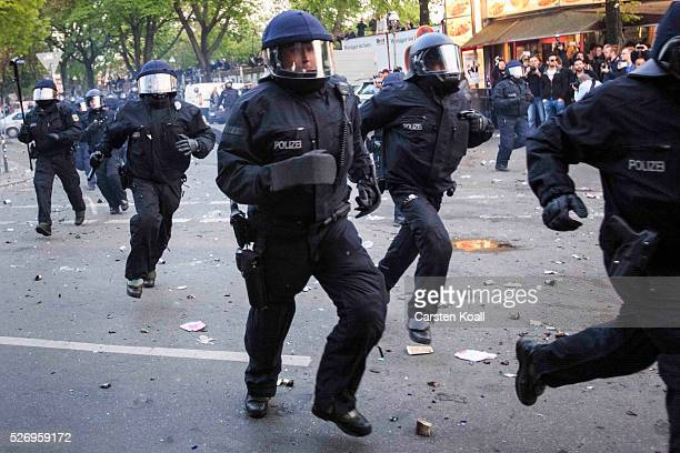 German riot policemen rush forward during clashes after a march on May Day on May 2016 in Berlin Germany Tens of thousands of people across Germany...