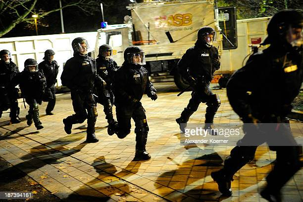 German riot policemen wearing riot gear stand react to clashes of football fans of Eintracht Braunschweig prior the Bundesliga match between Hannover...