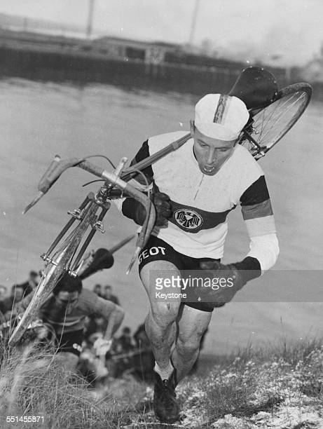 German road bicycle racer Rolf Wolfshohl running through water with his bike on his shoulder taking part in the CrossCycle World Championships in...