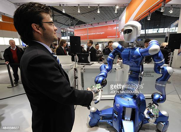 German robotics engineer Thomas Wimboeck shakes hands with the 'mobile robotic system' Rollin' Justin at the world's biggest hightech fair the CeBIT...