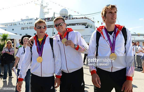 German rowing athletes Karl Schulze Andreas Kuffner and Philipp Wende show their Olympic gold medals at the port of Hamburg northern Germany as they...