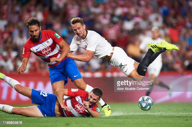 German Sanchez and Domingo Duarte of Granada CF compete for the ball with Luuk de Jong of Sevilla FC during the Liga match between Granada CF and...