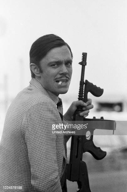 German schlager singer Juergen Drews playing a mafia member with a machine gun, Germany circa 1980.