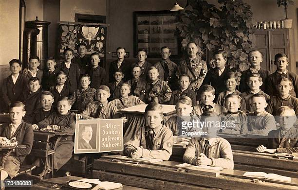 A German school room with boys and their teacher some in military uniforms with a portrait of Adolf Hitler circa 1936