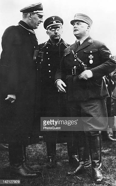 German Schutzstaffel Gruppenfuhrer Kurt Daluege speaks to Sturmabteilung commander Ernst Rohm as SS commander Heinrich Himmler listens Germany early...