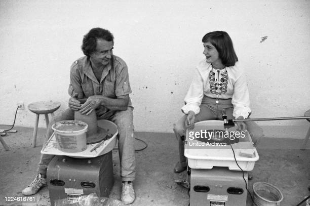 German sculptor Erno Wiedenmann showing his pottery arts to young singing talent Patty Landers at Traunstein, Germany, 1970s.
