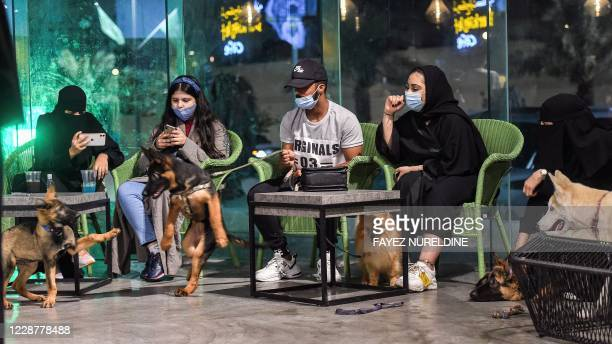 """German Shepherds play together as their mask-clad owners sit by at the """"Barking Lot"""" cafe in Saudi Arabia's eastern Gulf city of Khobar, 450..."""