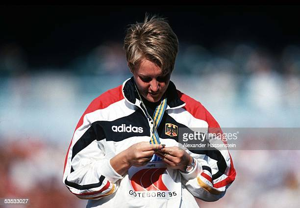 German shot putter Astrid Kumbernuss looks at her gold medal during the Athletics World Championships 1995 on August 7, 1995 in Goteborg, Sweden.