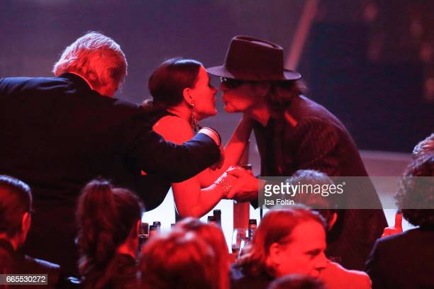 German singer and award winner Udo Lindenberg kisses his girlfriend Tine Acke during the Echo award show on April 6 2017 in Berlin Germany