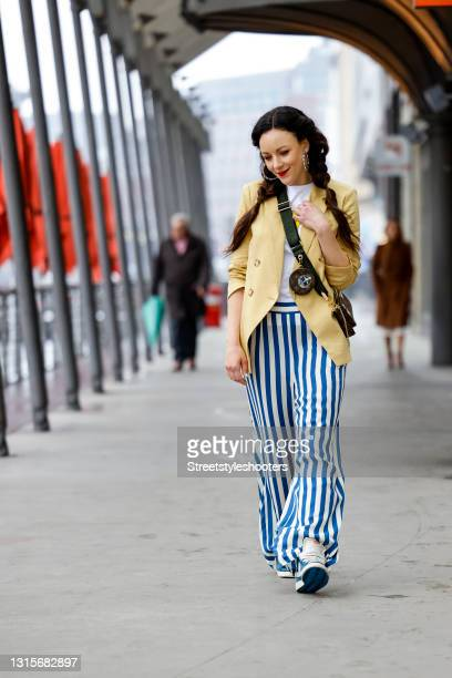 German singer Jasmin Wagner wearing a white shirt with a yellow smiley face by Kule, a yellow blazer by Veronica Beard, blue and white striped pants...