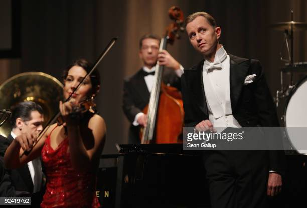 German singer Max Raabe performs with his Palast Orchester orchestra at a photocall for the release of his new DVD 'Heute Nacht Oder Nie' at...
