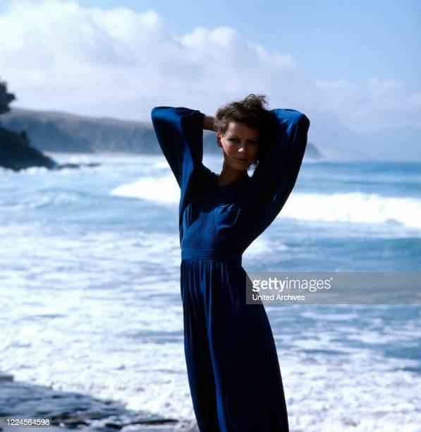 German singer Su Kramer posing on the beach in a blue dress, mid 1970s.