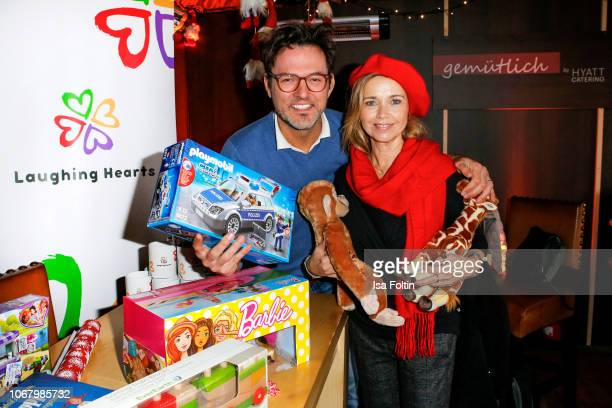 German singer Tobey Wilson and German actress Tina Ruland wrap a present for children in need during the Laughing Hearts Charity Christmas event at...