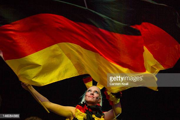 German soccer fan cheers with German flags at the end of their team's first game of the Euro 2012 at a public viewing zone called 'fan mile' on June...