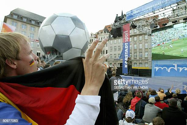 German soccer fans cheer their football team as the Euro2004 group D football match against Latvia is displayed on a giant screen at the market...