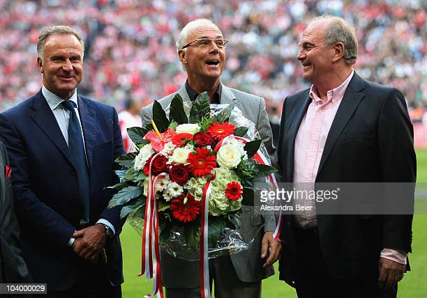 German soccer legend Franz Beckenbauer sings as KarlHeinz Rummenigge and the president of Bayern Muenchen Uli Hoeness smile before the Bundesliga...