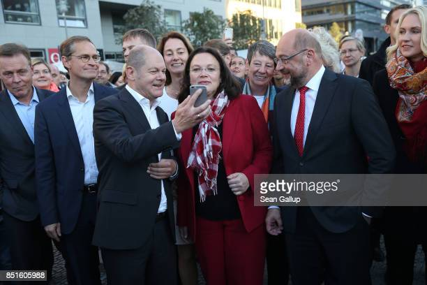 German Social Democrat and chancellor candidate Martin Schulz looks at the smartphone held by SPD member Olaf Scholz as other leading SPD members...
