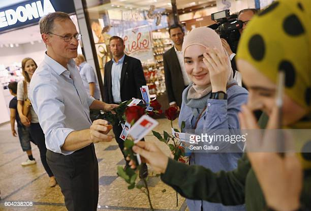German Social Democrat and current Berlin Mayor Michael Mueller distributes roses to young Muslim women as he campaigns in Berlin state elections at...