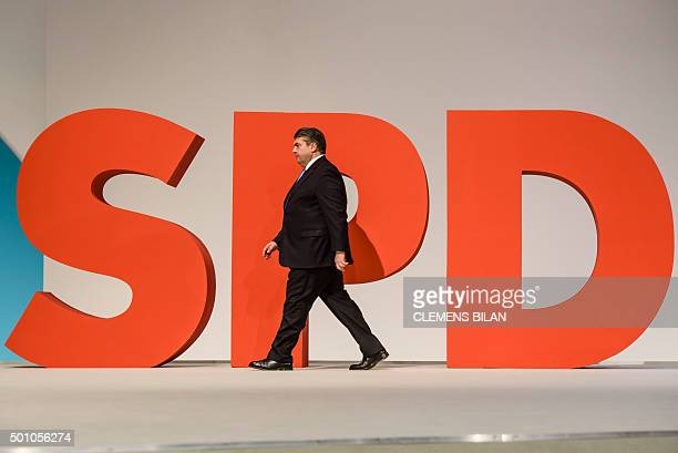 German Social Democratic Party leader German Vice Chancellor Economy and Energy Minister Sigmar Gabriel walks by a giant logo of his party at the SPD...