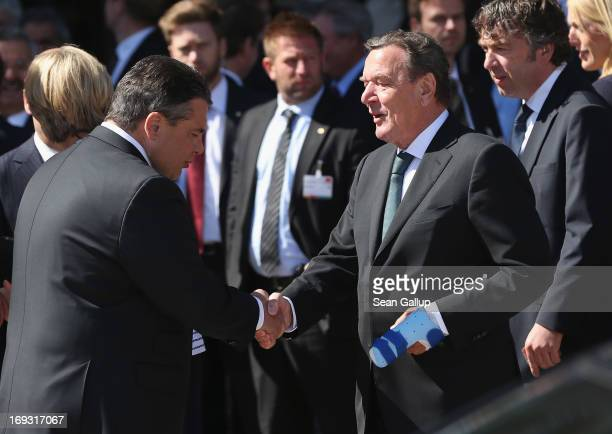 German Social Democrats Chairman Sigmar Gabriel greets former German Chancellor Gerhard Schroeder as Schroeder arrives at the 150th anniversary...