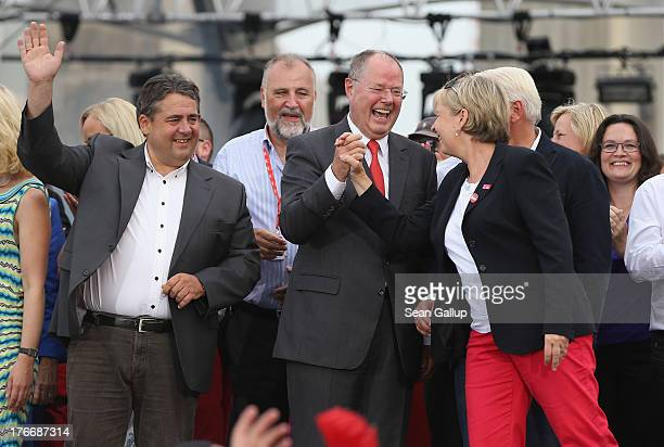German Social Democrats chancellor candidate Peer Steinbrueck clutches hands with colleague Hannelore Kraft while standing on stage with SPD Chairman...