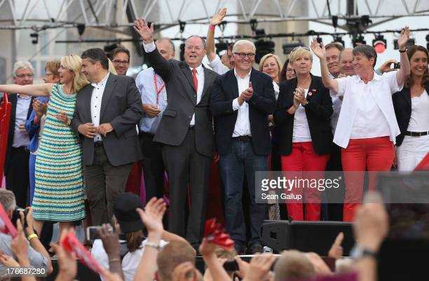 German Social Democrats chancellor candidate Peer Steinbrueck waves to supporters while standing on stage with other leading party members, including...