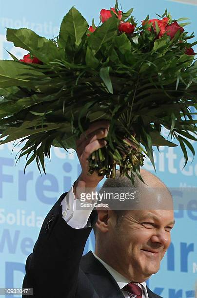 German Social Democrats Hamburg mayoral candidate Olaf Scholz holds up flowers at a reception at SPD headquarters following his election victory the...