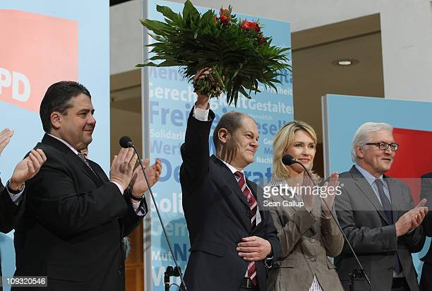 German Social Democrats Hamburg mayoral candidate Olaf Scholz holds up flowers at SPD headquarters as party Chairman Sigmar Gabriel party board...