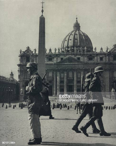 A German soldier and two Italian colonial guards in St Peter's Square on the border between Rome and the Vatican World War II from L'Illustrazione...