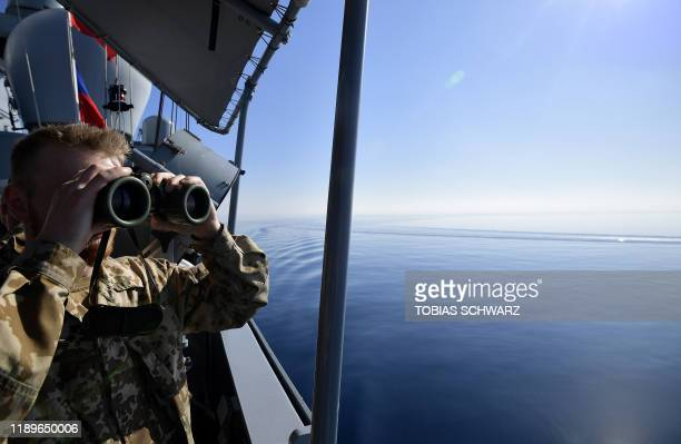 A German soldier at the United Nations Interim Force in Lebanon watches with binoculars aboard a German Navy corvette on December 19 2019 during...