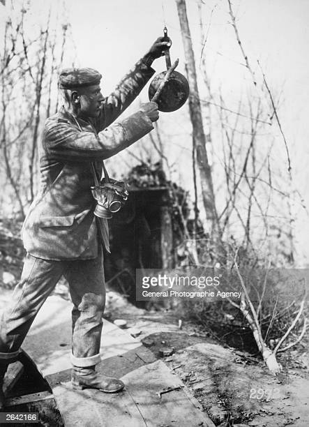 A German soldier banging on a suspended frying pan to warn of a gas attack