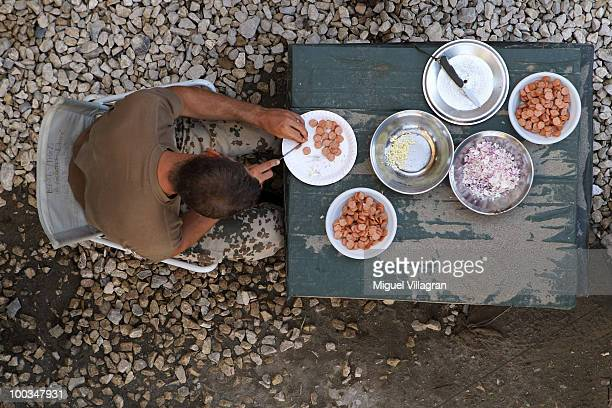 German soldier cuts sausages for diner at the police headquarters on May 23 2010 in Chahar Darreh Afghanistan Germany has more than 4500 military...