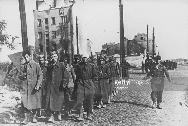 A German soldier guarding captured members of the Polish resistance after their capitulation at the end of the Warsaw Uprising against the Nazi...
