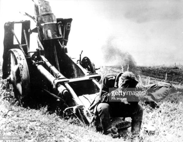 A German soldier in the Orel Salient sitting in despair on the remains of an artillery piece in the wake of the Battle of Kursk A dead comrade lies...