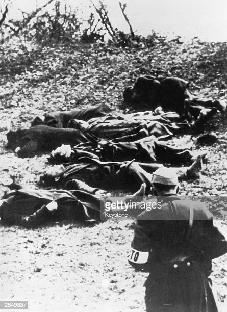 A German soldier inspects the bodies of a group of Jewish men executed by firing squad by the banks of the Danube in Hungary at the end of World War...