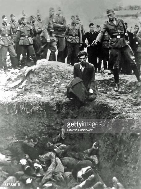 A German soldier is about to shoot a Jewish man in Vinnytsia 1941 The victim is sitting on the edge of an excavation with many dead bodies inside...