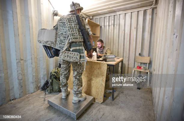 A German soldier is weighed with his gear before boarding a transport aircraft at the port of Kunduz Afghanistan 04 October 2013 After the official...