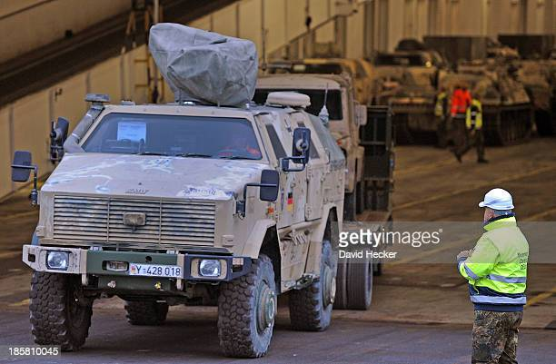 German soldier looks at a Dingo armoured vehicle returning from Afghanistan and being unloaded from a ship on October 25 2013 in Emden Germany...
