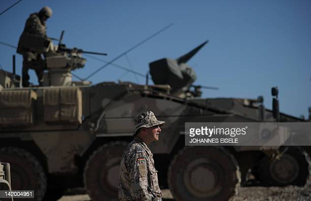 A German soldier looks on as an officer calibrates the weapons of a Boxer tank in the OP North base near Baghlan on March 28 2012 Around 500 German...