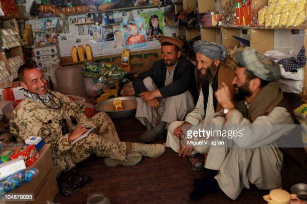 German soldier of a CIMIC unit talks to Afghan men to ask them for their needs during a regular patrol on October 6 2010 near Feyzabad Afghanistan...