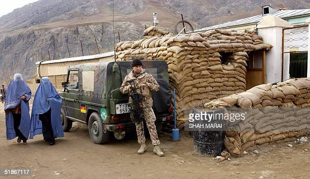 German soldier of the International Security Assistance Force is passed by two burqa clad Afghan women as he stands guard at the entrance to a German...