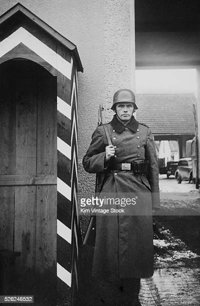 A German soldier stands at attention at the entrance to a military compound during World War II