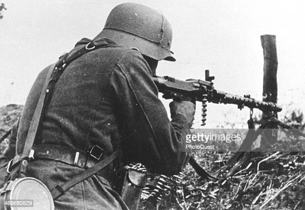 A German soldier uses a machine gun against the enemy who is located in the hedges surrounding Verdun Monfauvon France June 13 1940