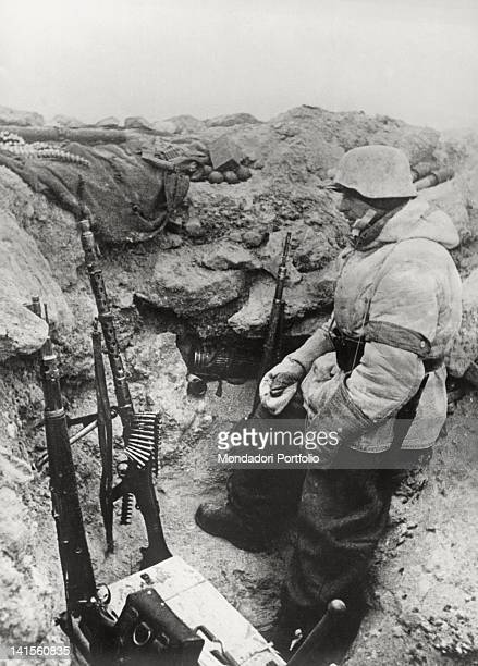 German soldier with a MG 42 machine gun and two rifles is on call in a trench in the Vorosilovgrad area. Soviet Union, 1943