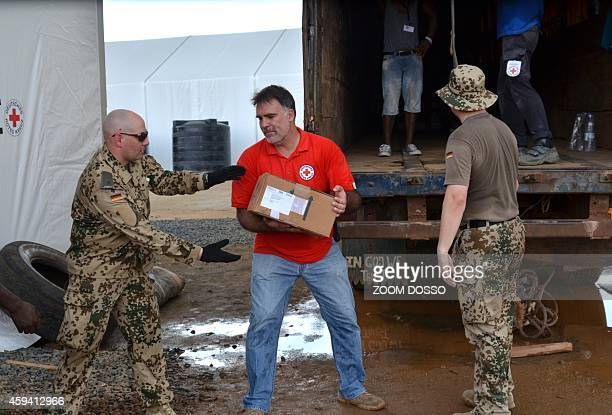 German soldiers along side German Red Cross workers unload a truck as they construct an Ebola treatment center on November 21 in the Liberian capital...
