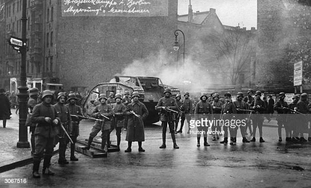 German soldiers clustered around a tank in a Berlin street during a troubled period of the Weimar Republic