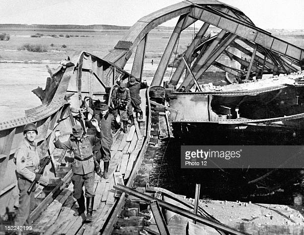 German soldiers hold hands up in surrender April 29 as they cross a narrow plank path on a wrecked bridge spanning the Elbe River in the Tangermunde...