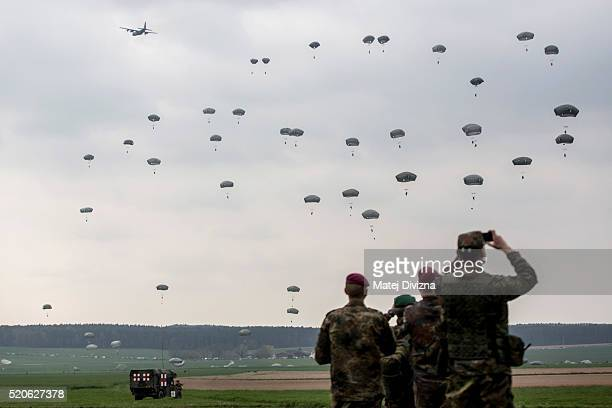 German soldiers look at paratroopers from the US Army 173rd Airborne Brigade the UK's 16 Air Assault Brigade and Italian Folgore Airborne Brigade as...