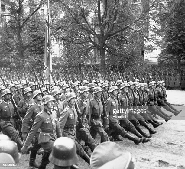 German soldiers march through a street in Poland after the German invasion of Poland in 1939.